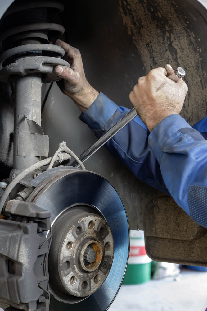 mechanic putting new brake discs on car