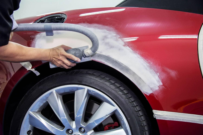 car bodywork specialist sanding down dent in red car