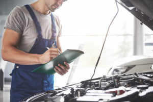 mechanic performing MOT test on vehicle