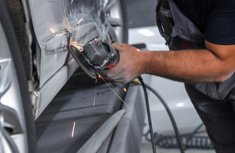 Mechanic using angle grinder on car body