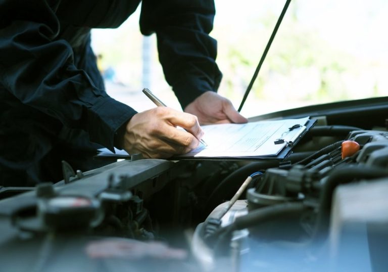 man with clipboard on car engine